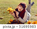 Girl lying on ground with yellow leaves 31695983