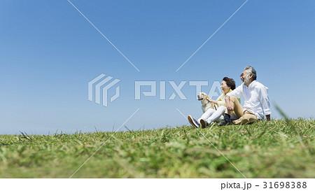 シニア夫婦と犬 草原と青空 31698388