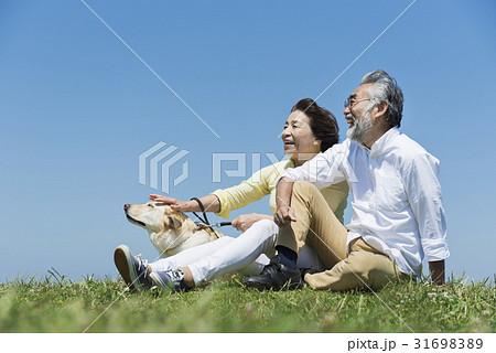 シニア夫婦と犬 草原と青空 31698389