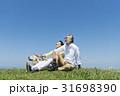 シニア夫婦と犬 草原と青空 31698390