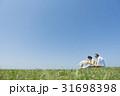 シニア夫婦と犬 草原と青空 31698398