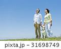 シニア夫婦と犬 草原と青空 31698749