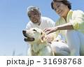 シニア夫婦と犬 草原と青空 31698768