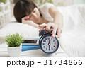朝、目覚まし時計を止める女性 起床イメージ 31734866