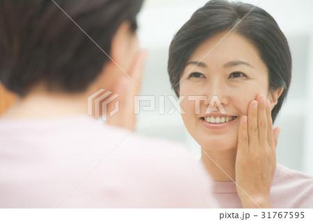 鏡を見る笑顔の中年女性 31767595