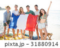 Friends holding French flag while standing at beach 31880914