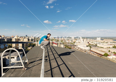 Roofer sits on the railing 31920581