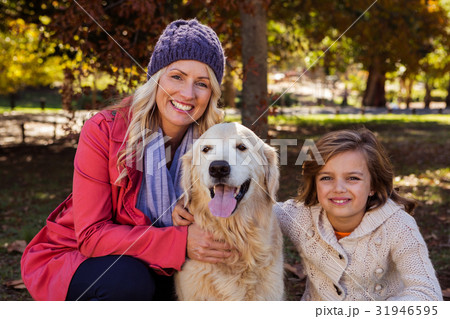 Mother and daughter caressing their dog 31946595