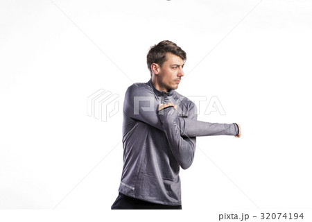 Fit man in gray sweatshirt stretching arms, studio 32074194