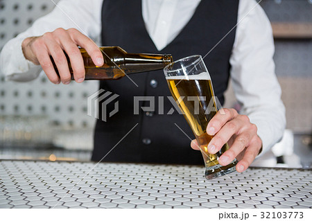 Bartender pouring beer on glass 32103773