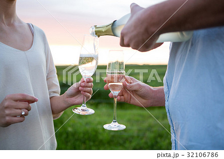 Close-up of couple having champagne in fieldの写真素材 [32106786] - PIXTA