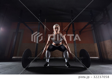 Muscular young fitness woman lifting a weight in 32237058