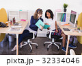 Businesswomen discussing while working in office 32334046