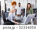 Mature businesswoman with colleagues in office 32334050