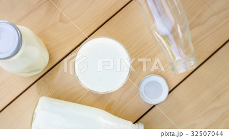 a bottle and glass of milk on a wooden table.の写真素材 [32507044] - PIXTA