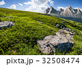 meadow with huge stones on top of mountain range 32508474