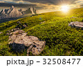 meadow with huge stones on top of mountain range 32508477