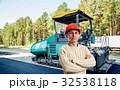 Workman with asphalt-placing machine 32538118