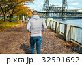 Man walking along the riverwalk in Portland city at autumn 32591692