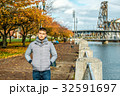 Man walking along the riverwalk in Portland city at autumn 32591697