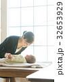 スーツ姿の女性と赤ちゃん 32653929