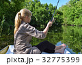 Girl in a boat is fishing in the lake 32775399