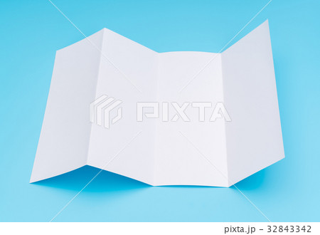 four fold white template paper on blue background の写真素材