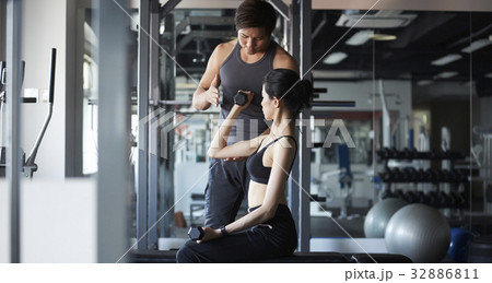 a photo of a man guiding a woman working out at gym 32886811