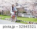 桜並木をサイクリングする女性 32945321