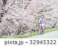 桜並木をサイクリングする女性 32945322