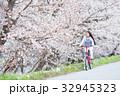 桜並木をサイクリングする女性 32945323