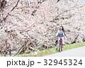 桜並木をサイクリングする女性 32945324