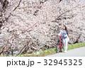 桜並木をサイクリングする女性 32945325