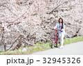 桜並木をサイクリングする女性 32945326