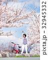 桜並木をサイクリングする女性 32945332