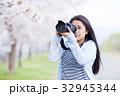 満開の桜と女性カメラマン 32945344
