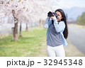満開の桜と女性カメラマン 32945348
