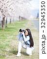 満開の桜と女性カメラマン 32945350