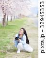 満開の桜と女性カメラマン 32945353