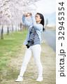 満開の桜と女性カメラマン 32945354