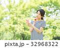 携帯電話を持つ女性(緑背景) 32968322