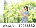 携帯電話を持つ女性(緑背景) 32968332
