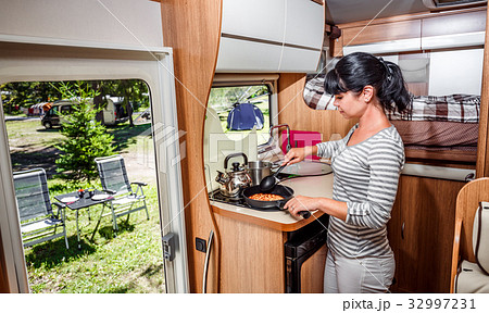 Woman cooking in camper, motorhome interior 32997231