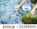 ペットボトルに清水を汲む女の子の手 33108493