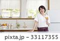 キッチンでグラスを傾ける女性 33117355