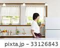 キッチンでグラスを傾ける女性 33126843