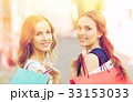 happy women with shopping bags walking in city 33153033