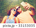 happy couple taking selfie on smartphone at summer 33153035