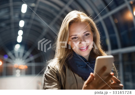 Woman in the city at night holding smartphone 33165728