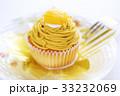 黄色い甘栗の乗ったカップケーキサイズの市販のモンブラン フォークを添えて 33232069